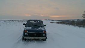 Blauwe Russische off-road auto Lada Niva 4x4 VAZ 2121/21214 ritten op het sneeuwgebied stock footage