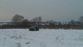 Blauwe Russische off-road auto Lada Niva 4x4 VAZ 2121/21214 ritten op het sneeuwgebied stock videobeelden