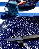 Blauwe schotel met vork, mes en kop Stock Foto
