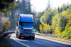 Blauwe semi vrachtwagen en vlakke bedaanhangwagen op zonnig groen en goud aut stock afbeeldingen