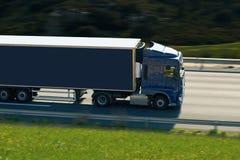 Blauwe semi vrachtwagen op de weg Stock Fotografie