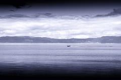 Blauwe sepia boot op overzeese van Noorwegen landschapsachtergrond Stock Afbeelding
