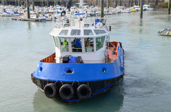 Blauwe sleepbootboot in een jachthaven stock fotografie