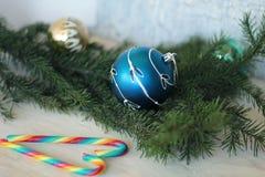 Blauwe snuisterij op Kerstmisboom en suikergoedriet Stock Fotografie