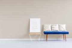 Blauwe sofa tegen pastelkleurmuur royalty-vrije stock afbeelding