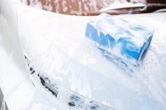 Blauwe spons en zeep over de auto voor was Voorzijde die van de motorkap worden de schoongemaakt royalty-vrije stock afbeeldingen