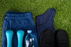 Blauwe sportkleding, zwarte tennisschoenen, domoren en een fles water, tegen de achtergrond van gras Royalty-vrije Stock Foto