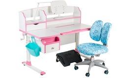 Blauwe stoel, roze schoolbank, blauwe mand, bureaulamp en zwarte steun onder benen Stock Foto's