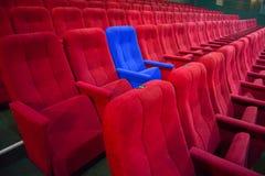 Blauwe stoel tussen rijen van rode zetels Stock Foto's