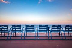 Blauwe stoelen op Promenade des Anglais in Nice Frankrijk stock foto's