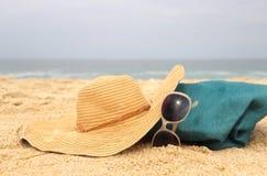 Blauwe strandzak op de zeekust en strohoed Stock Foto