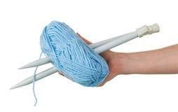 Blauwe streng van wol en breinaalden in vrouwelijke die handen op wit worden geïsoleerd royalty-vrije stock afbeelding