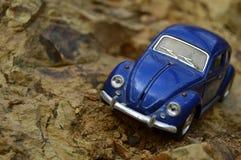 Blauwe stuk speelgoed auto op berg Stock Afbeeldingen