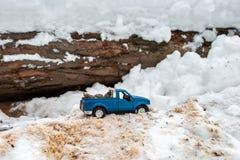 Blauwe stuk speelgoed pick-up in zaagmolen Geplakt bij sneeuwbank en zaagsel Dragende sparappel in de rug van een autolichaam royalty-vrije stock foto