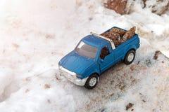 Blauwe stuk speelgoed pick-up in zaagmolen Geplakt bij sneeuwbank en zaagsel Dragende sparappel in de rug van een autolichaam royalty-vrije stock afbeeldingen