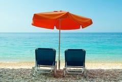 Blauwe sunbeds en oranje paraplu (parasol) op Paradijsstrand binnen Stock Foto