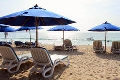 Blauwe sunbeds met paraplu dichtbij het overzees Stock Fotografie