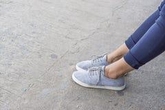 Blauwe tennisschoenen op Aziatische vrouwelijke voeten royalty-vrije stock afbeelding
