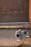 Blauwe tennisschoenen op deurmat Stock Foto