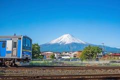 Blauwe trein op spoorwegsporen met Onderstel Fuji Stock Foto