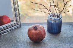Blauwe vaas met boomtakken en een spiegel, en granaat Stock Foto's