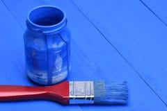 Blauwe verf in een kruik met borstel stock foto's