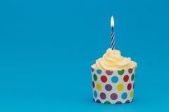 Blauwe verjaardag cupcake met blauwe kaars Stock Foto's
