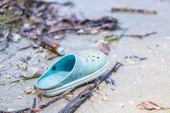 Blauwe verlaten schoen op het strand Stock Foto
