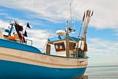 Blauwe vissersboot op de kust Stock Fotografie