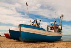 Blauwe vissersboot op de kust Stock Foto