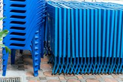 Blauwe vouwbare lijsten en plastic die stoelen buiten op concrete blokken worden gestapeld stock foto's