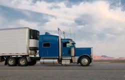 Blauwe vrachtwagen die zich op een weg beweegt Stock Fotografie