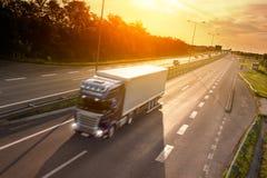 Blauwe vrachtwagen in motieonduidelijk beeld op de weg Royalty-vrije Stock Afbeeldingen