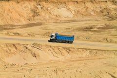 Blauwe vrachtwagenbewegingen langs een zandkuil op een zonnige dag Stock Fotografie