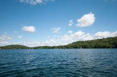Blauwe water en hemel met wispy wolken Stock Foto's