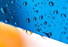 Blauwe waterdalingen op glas Stock Foto