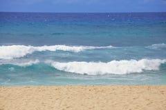 Blauwe wateren en golven op een Hawaiiaans strand op zonnige dag Stock Afbeelding