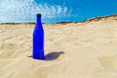 Blauwe waterfles die zich in droog geel zand bevinden Stock Afbeeldingen