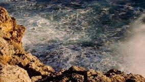 Blauwe watergolven en een rotsachtig strand stock footage