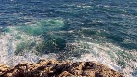 Blauwe watergolven en een rotsachtig strand stock videobeelden