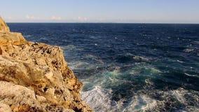Blauwe watergolven en een rotsachtig strand stock video
