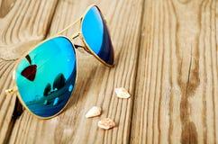 Blauwe weerspiegelde zonnebril met bezinning van martini-glas op stock foto