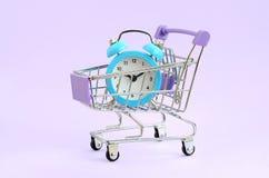 Blauwe wekker in supermarktkarretje op violette achtergrond royalty-vrije stock afbeeldingen