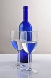 Blauwe Wijnfles en Glazen Stock Foto