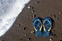 Blauwe wipschakelaarsandals op het strand Stock Afbeelding