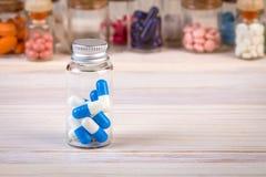 Blauwe witte gekleurde capsules in glascontainer Stock Afbeeldingen