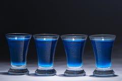 Blauwe wodka in vier glazen Royalty-vrije Stock Foto's