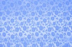 Blauwe zijde met bloemen als achtergrond Stock Afbeeldingen