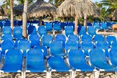 Blauwe zitkamers op een zandstrand Royalty-vrije Stock Foto's