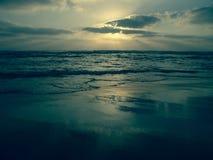 Blauwe zonsondergang onder een bewolkte hemel op een zandig strand met bezinningen over het natte zand royalty-vrije stock afbeelding